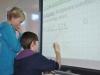 Zwei Schüler beweisen sich als wahre Rechenmeister an der interaktiven Tafel.