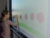 Eine Schülerin entdeckt das interaktive Whiteboard zum Zeichnen.